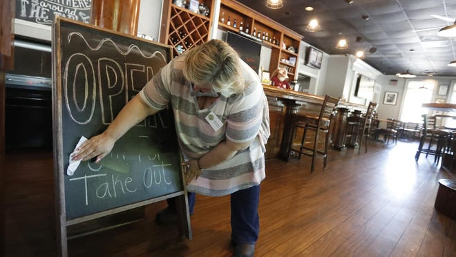 Mary Spoto, general manager of Madison Chop House Grille, changes the sign as she and her staff prepare to shift from take out only to dine-in service Monday, April 27, 2020, in Madison, Ga. Some Georgia restaurants were reopening for limited dine-in service as more restrictions against the coronavirus are loosened in the state. Movie theaters on Monday can welcome customers and limited in-restaurant dining may resume.