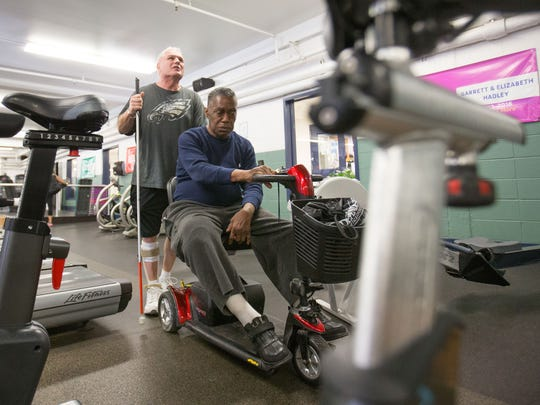 Ronnie Felton leads Bruce Drainer to an exercise machine