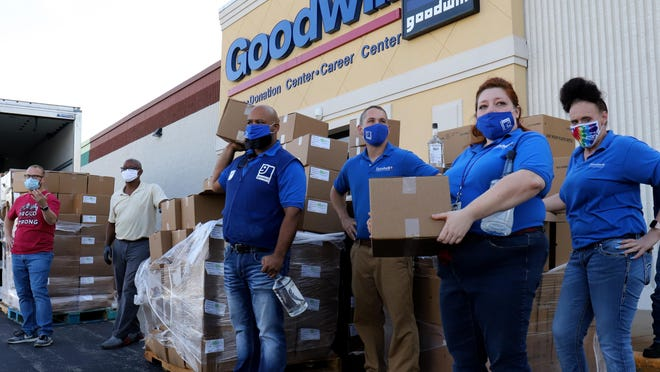 Goodwill staff members work to distribute free USDA dairy boxes and bottles of hand sanitizer during a River Valley Regional Food Bank drive-thru pop-up pantry, Monday, August 17, 2020, at the Goodwill facility on S 74th St. Tracy Engel, Food Bank director said that the Food Bank serves eight counties in Arkansas and has seen a 50% increase in distributed over the same period in 2019.