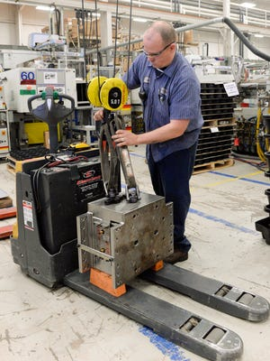 Nate Watkins, set-up technician, operates an overhead crane to pick and place a molding tool into an injection molding machine for the next product to be manufactured at Kaysun Corp. in Manitowoc. Sue Pischke/HTR Media. Photo taken on Wednesday, Dec. 3, 2014.