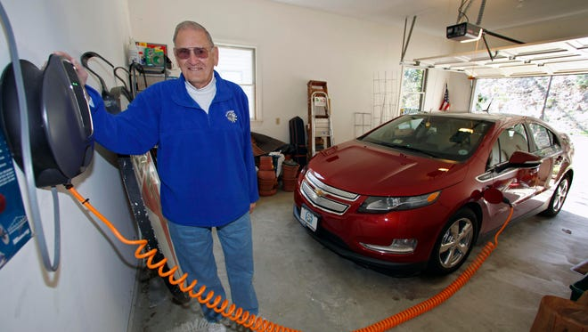 James Brazell poses with a charging unit for his Chevy Volt electric car at his home in Asheville, N.C., in 2011.