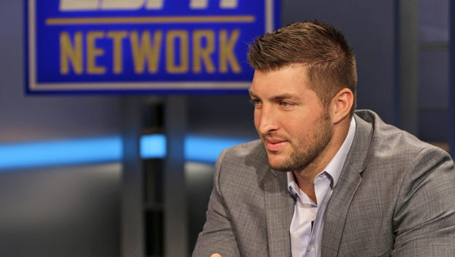 Tim Tebow answers a question during a interview on the set of ESPN's new SEC Network in Charlotte, N.C., Wednesday, Aug. 6, 2014. Tebow has a new job as a commentator for the SEC Network, but is still looking for work in the NFL as a quarterback. (AP Photo/Chuck Burton)