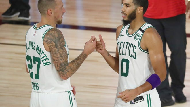 Celtics forward Jayson Tatum, right, and center Daniel Theis celebrate their series sweep of the Phiadelphia 76ers in Game 4 of the first round of the NBA Playoffs on Sunday in Lake Buena Vista, Fla.