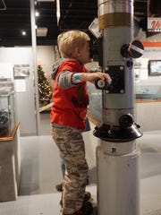 A child peers through a working periscope at the Door County Maritime Museum.