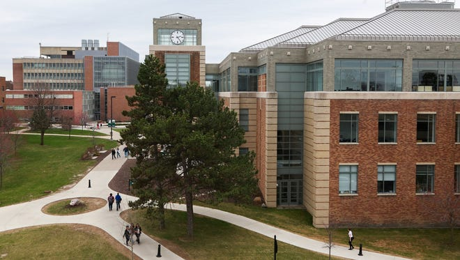 Students walk through the campus at Eastern Michigan University in Ypsilanti on Thursday, April 16, 2015.