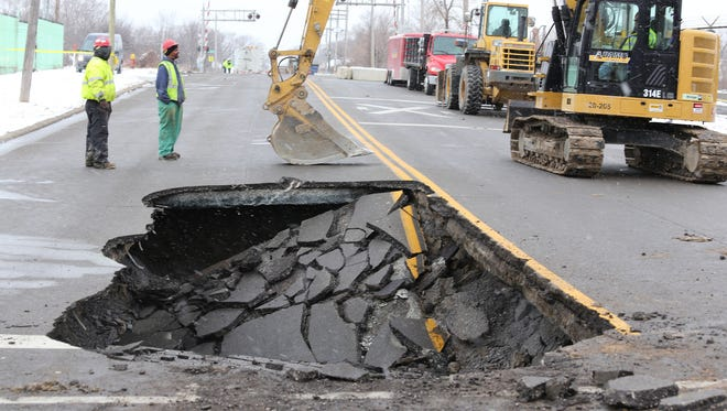 An excavator and workers are seen working on a sinkhole on the west side of Detroit on Tireman at  Greenfield on Wednesday, March 3, 2016.