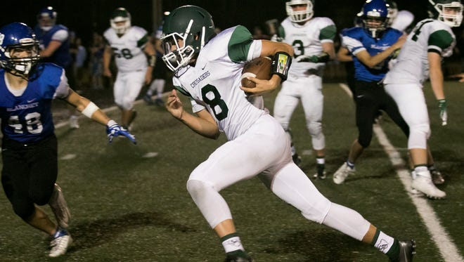 Salem Academy quarterback Colton Daniels tucks in the ball and runs for a touchdown in the game against Blanchet on Friday, Sept. 16, 2016, at Salem Academy. Daniels' touchdown late in the fourth quarter, with 55 seconds left on the clock, helped secure the Salem Academy Crusaders 14-10 victory over Blanchet.