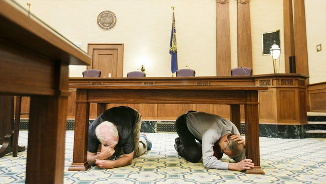 Senate President Peter Courtney (left) and Oregon Supreme Court Chief Justice Thomas Balmer (right) demonstrate proper Drop, Cover and Hold techniques as they hold onto one table leg and keep a hand over their head for protection as they participate in the Great Oregon Shake-out earthquake drill on Thursday, Oct. 20, 2016.