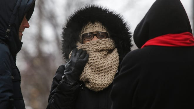 Valerie Coleman (center) of Detroit covers her face while waiting for a bus on Woodward near Congress in downtown Detroit on November 18, 2014 as cold weather and snow moved into the area.
