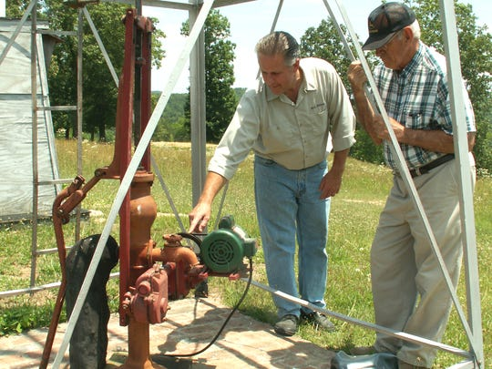 In this 2006 photo, Dale Borel points out a feature of the working windmill pump at Bo's Hollow to Dan Fortner, a recent visitor with a church group from Berean Baptist Church in Springfield.