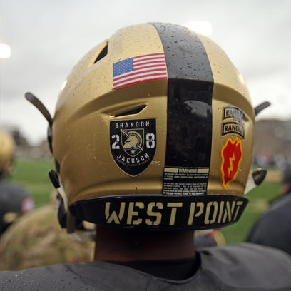 An Army player wears a helmet decal honoring defensive