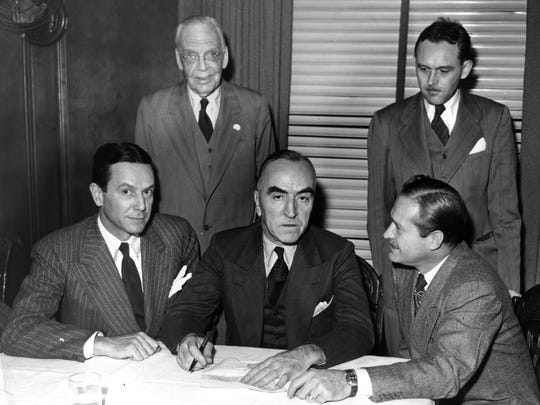 """Front row, from left: Tony Hulman Jr., Capt. Eddie Rickenbacker and three-time Indianapolis 500 winner Wilbur Shaw sign the formal papers of transfer for the Indianapolis Motor Speedway on Nov. 15, 1945.  Hulman bought the track for $750,000.  Shaw became the speedway president. Watching from left were P.E. """"Pop"""" Myers and Joe Cloutier, who would become president of the speedway in 1977."""