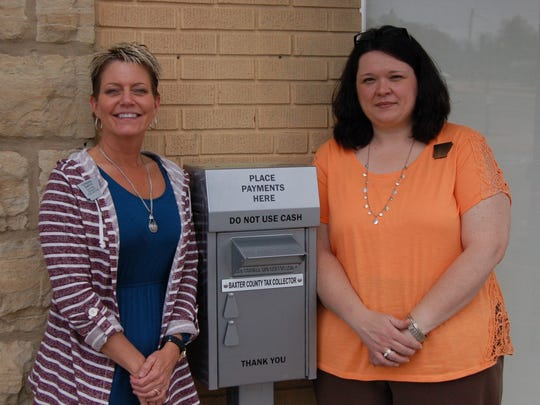 Baxter County Tax Collector Teresa Smith (left) and Chief Deputy Collector Yvette Sigafus flank the new overnight drop box for the Collector's Office.