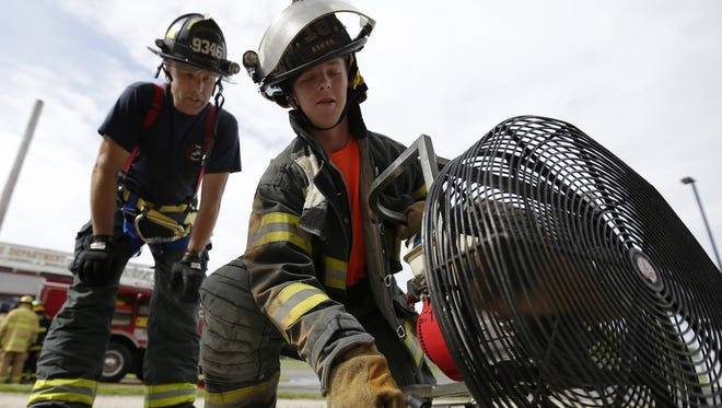 Appleton firefighter Tim Lutz, left, works with high school student Cade Esker on venting a structure.