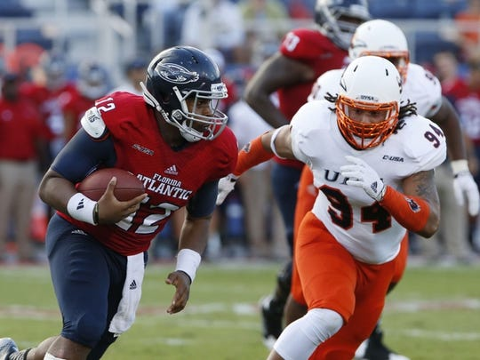 Sep 27, 2014; Boca Raton, FL, USA; Florida Atlantic Owls quarterback Jaquez Johnson (12) runs with the ball as UTSA Roadrunners defensive end Codie Brooks (94) defends in the second quarter at FAU Football Stadium. Mandatory Credit: Robert Mayer-USA TODAY Sports
