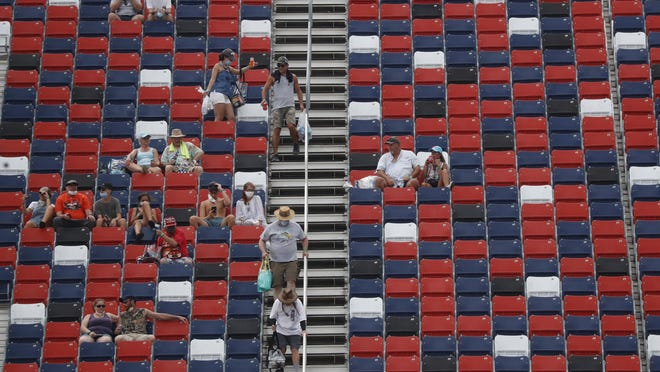 Fans dot the stands prior to a NASCAR Cup Series auto race Sunday at Talladega Superspeedway. Up to 5,000 were expected to be admitted to the track but rain forced the postponement of the race until Monday.