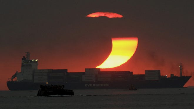 The moon blocks much of the sun in a partial solar eclipse as it sets over a bay in Manila in 2009. (AP Photo/Aaron Favila)