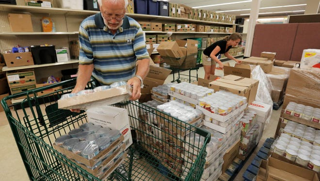 Volunteer Jim Retzloff puts cans of tuna into a cart to be put out on the shelves at the Oshkosh Area Community Pantry in this 2016 file photo.
