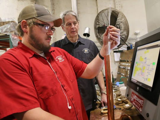 Russ Klisch (right), owner of Lakefront Brewery, looks over a testing process with brewer Ryan Hillesland at the Commerce St. brewery.