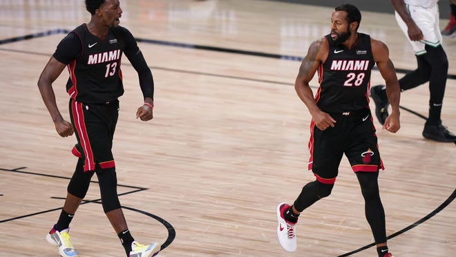 Miami Heat's Bam Adebayo (13) reacts to a basket along with teammate Andre Iguodala (28) during the second half Sunday, in Lake Buena Vista, Fla.