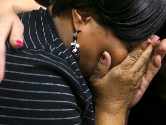 Nora Brisbon covers her face while crying during a media interview about her son, Rumain Brisbon, who was killed by a Phoenix police officer in December 2014.