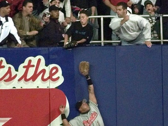 Baltimore Orioles' right fielder Tony Tarasco stretches for the ball as young Yankee fan Jeff Maier deflects it during Game 1 of the American League Championship Series against the New York Yankees in 1996.
