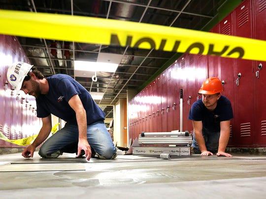 Cory Barr and Richard Finley of Twohig Flooring lay tile in St Mary's Springs Academy on Friday. A grand-opening celebration is scheduled from 1 to 4 p.m. Aug. 21.