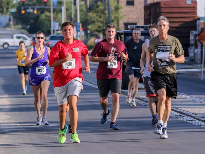 Runners make their way through downtown Pensacola during