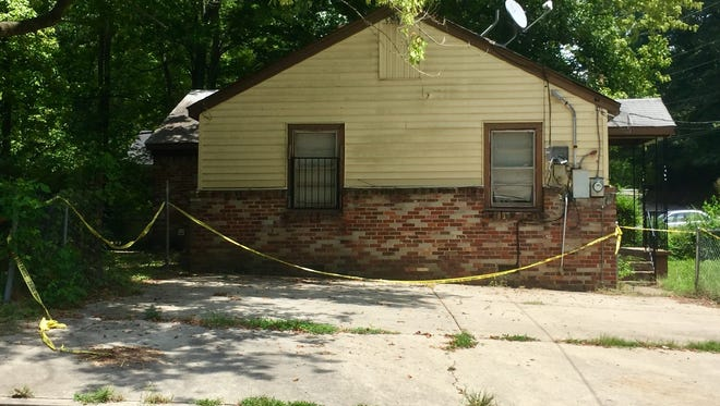 Caution tape surrounded the driveway and entrance of a house on Hawkins Mill Road where two died of gun shot wounds Saturday night.