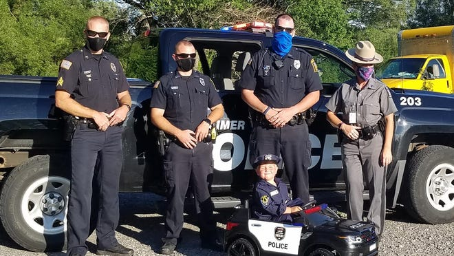 Abel Jones, 4, is pictured wearing his own Herkimer police officer uniform and seated in a miniature police vehicle Monday. Jones was given the gifts from the Herkimer Police Department as thanks for showing his support for police officers through his lemonade stand.
