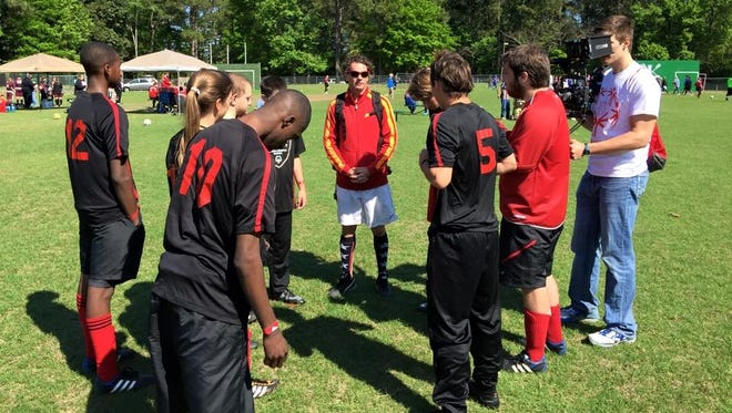 Lions United athletes and partners, led by Leon High School's Coach Scott Evans, gear up for a soccer match.