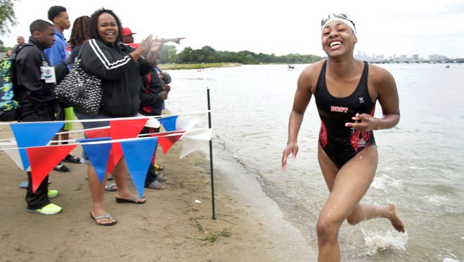 Danielle Green, 15,  with the Detroit Recreation Swim team finishes her 5k swim with a smile on her face at the 16th Annual Motor City Mile Swim at Belle Isle Beach in Detroit, Wednesday, July 8, 2015.