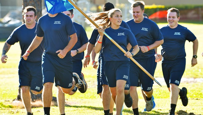 Saylor Murto carries a flag during running drills at Eastern Florida State College's Public Safety Institute in Melbourne.