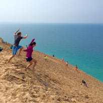 A couple takes a leap of faith at Michigan's iconic Sleeping Bear Dunes in Empire. Visitors walk part of the giant dune along Pierce Stocking Drive. Lake Michigan meets the dune at the shoreline in late August 2015.