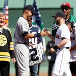 Boston Bruins great Bobby Orr, left, watches as Red Sox second baseman Dustin Pedroia presents Derek Jeter with a No. 2 second-base bag before the season finale at Fenway Park on Sunday.