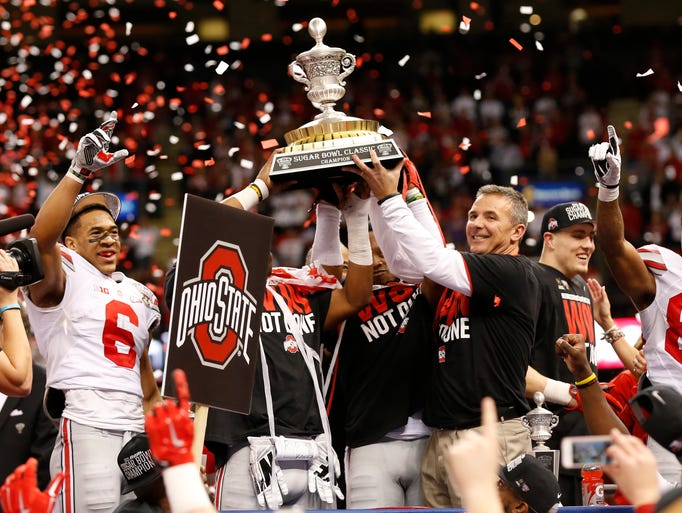 Ohio State Buckeyes head coach Urban Meyer hoists the