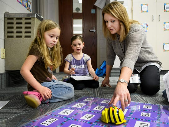 Katelyn Offerman (right) helps two of her first grade