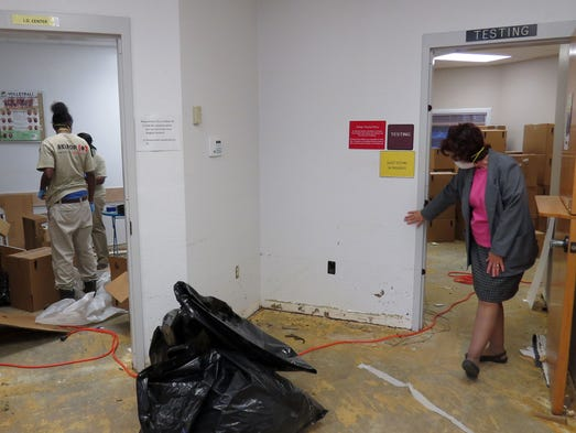 While cleanup continues, left, Pensacola State College Warrington Campus Dean Frances Duncan examines the water mark left by flood waters  that swept through much of the campus including building 3300 shown here.  Despite the damage the campus will be open Monday for its summer session.  Students should park in the west lot at PSC Warrington and report to building 3700.