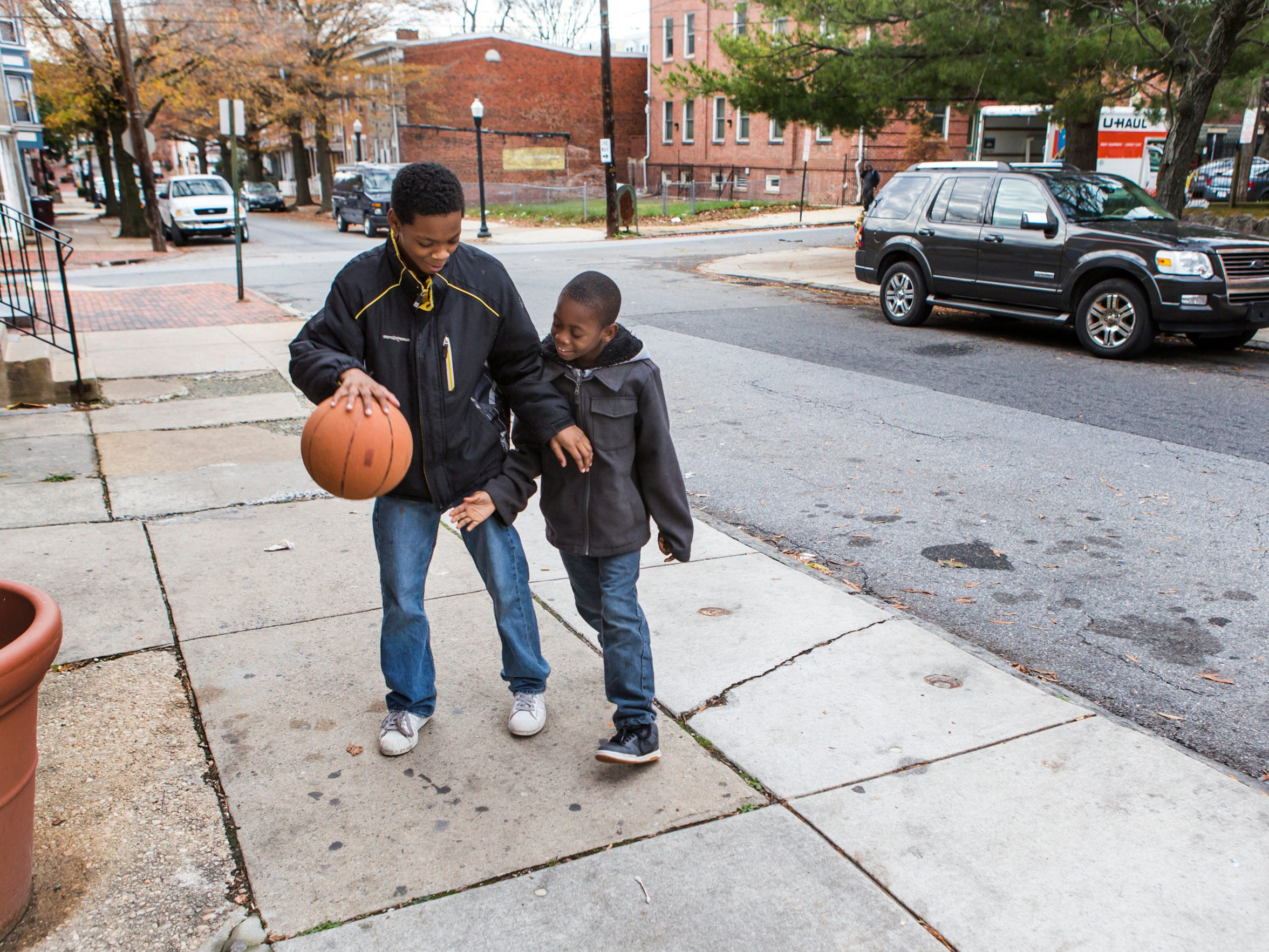 Walter Potter, 13, (left) plays basketball with his