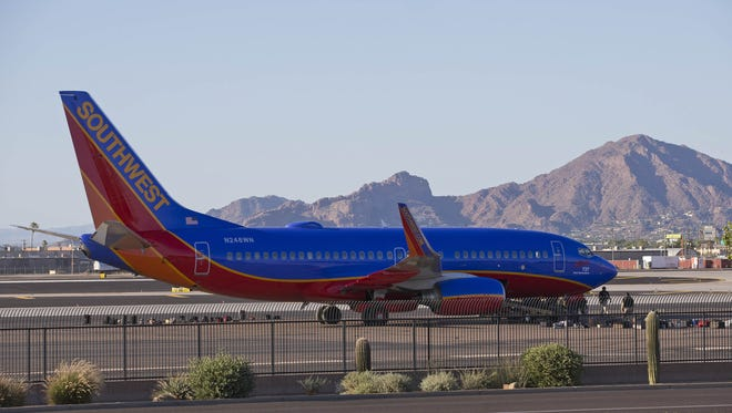 A Southwest Airlines plane is parked on the side of a runway at Phoenix Sky Harbor International Airport.