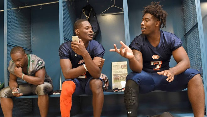 Callaway's James Williams (right) and Malik Heath relax with Pisgah running back Don Ragsdale (left) at the Dandy Dozen photo day at Mississippi Veterans Memorial Stadium in Jackson on July 26, 2017.