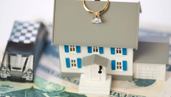 Toy house, car and cash with engagement ring