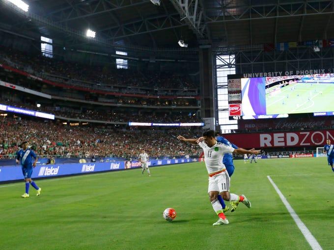 Mexico's Arlos Vela shields the ball from Guatemala's