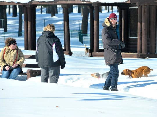 In this file photo, owners watch their dogs during the off-leash snow stomp for dogs at the splash pad in Marathon Park in Wausau. The Wausau and Marathon County Parks, Recreation and Forestry Department hosted the event as a fundraiser to provide reduced price pool passes and swimming lessons for local families.