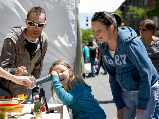 Dan Miller, Lila Miller, and Jessica Griffin, all of Horseheads, are captivated by glass works at a vendor's booth during last year's GlassFest in Corning.