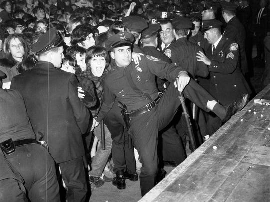 Fans try to reach through the police lines during the Rolling Stones concert at the Rochester Community War Memorial in 1965.