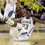 Michigan guard Caris LeVert reacts after making a basket during the second half of an NCAA college basketball game against Illinois in Ann Arbor, Mich., Tuesday, Dec. 30, 2014.