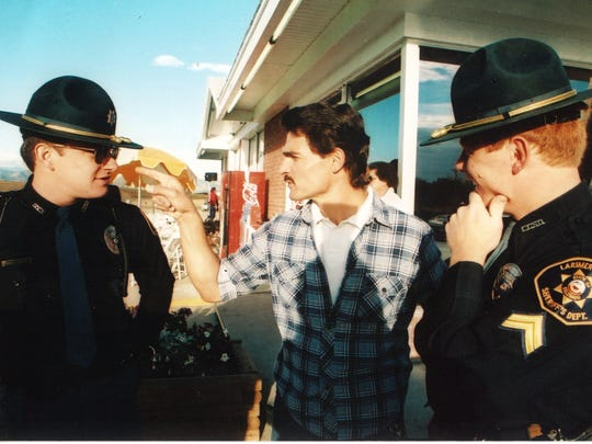 Owner Dennis Cortese interacts with Larimer County Sheriff's deputies during filming of Geraldo Rivera's segment on Debbie Duz Donuts.