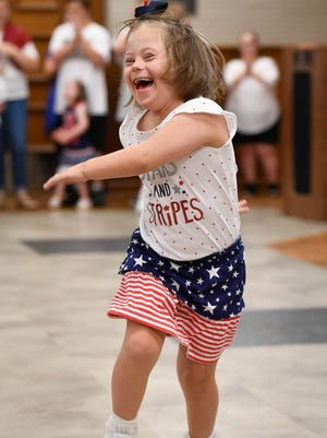 Mary Gries just can't help but smile as she dances solo across the stage at the SMILE on Down Syndrome dance recital at the Deaconess Health Science Building Wednesday, August 17, 2016.
