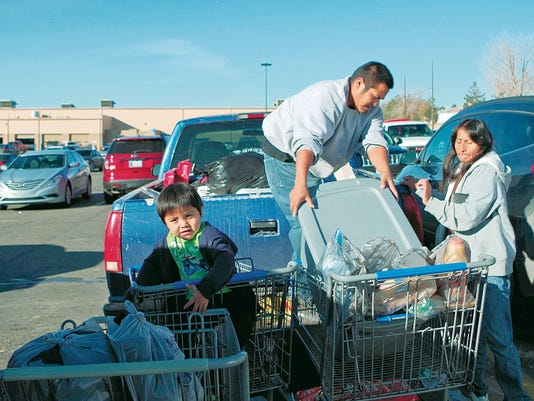 Allen Briant, center, and Cecelia Sandoval, right, load their truck on Black Friday morning in the parking lot of the eastern Walmart store in Farmington as Briant's son, Conan, looks on.